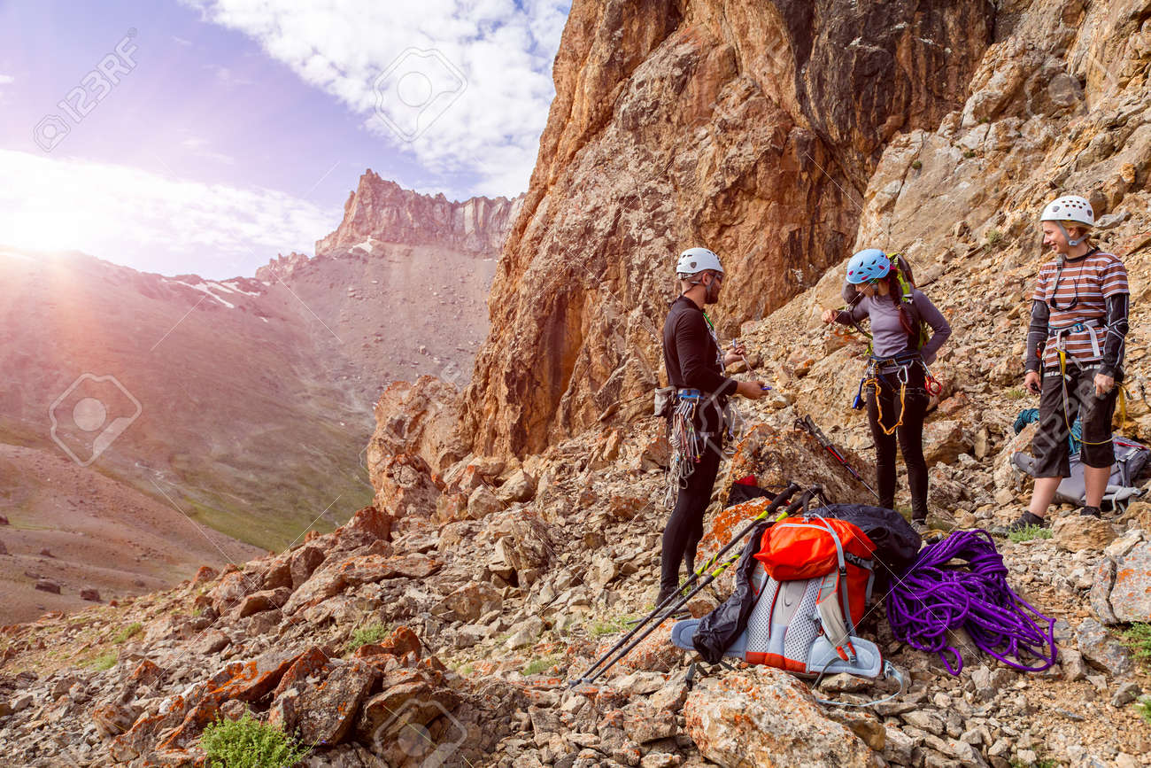 Three people male female placing gear packing backpacks staying on rocky terrain at beginning of Climbing Route on Mountains blue Sky and Sun Rising Background - 51510053