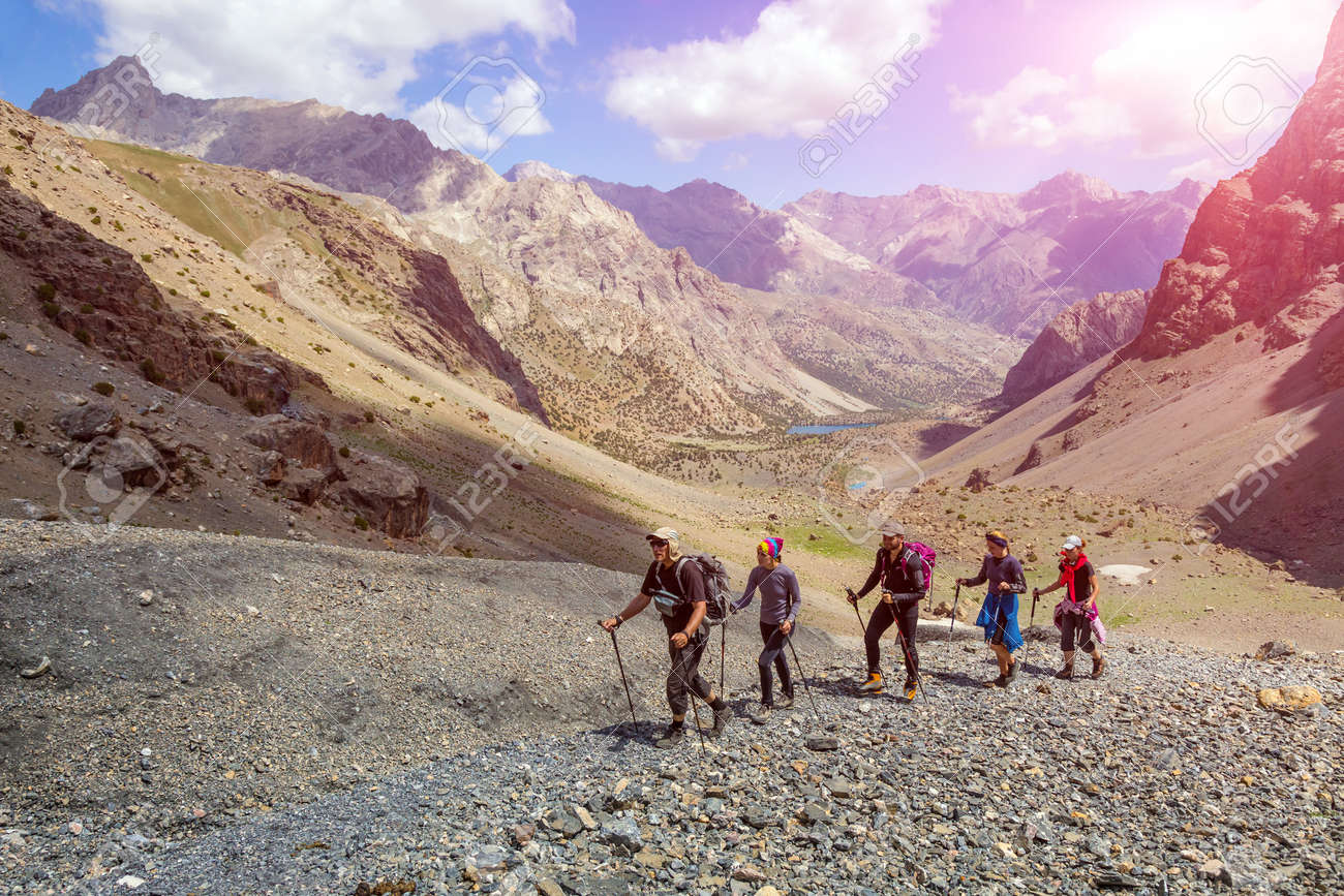 People walking along rocky footpath positive faces trekking gear poles sporty clothing bright panorama blue sky sunny day background - 52722337