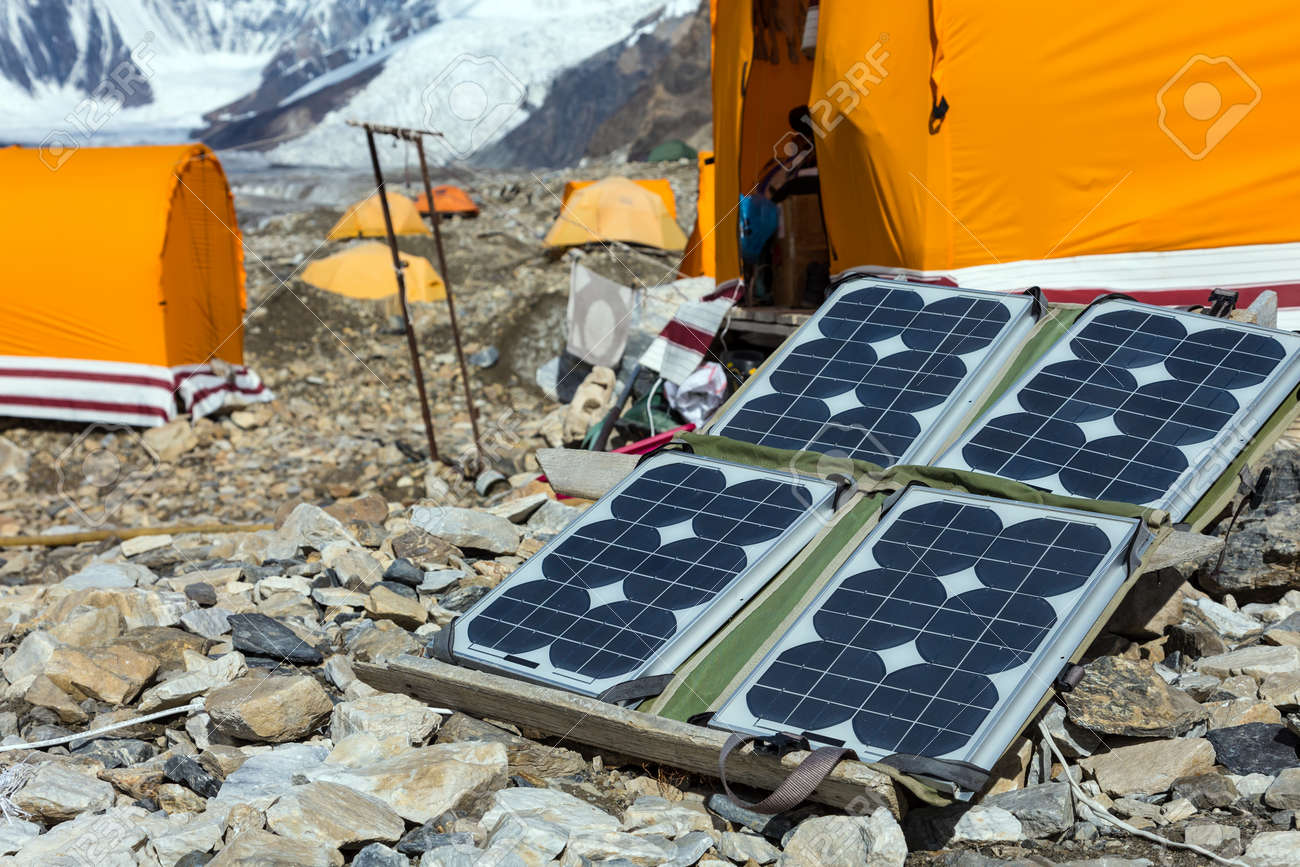 Solar Battery on Rocky Glacier Moraine for Electricity Supply of Sport Mountain Expedition in Wilderness Country with Camping Tents on Background - 56954648