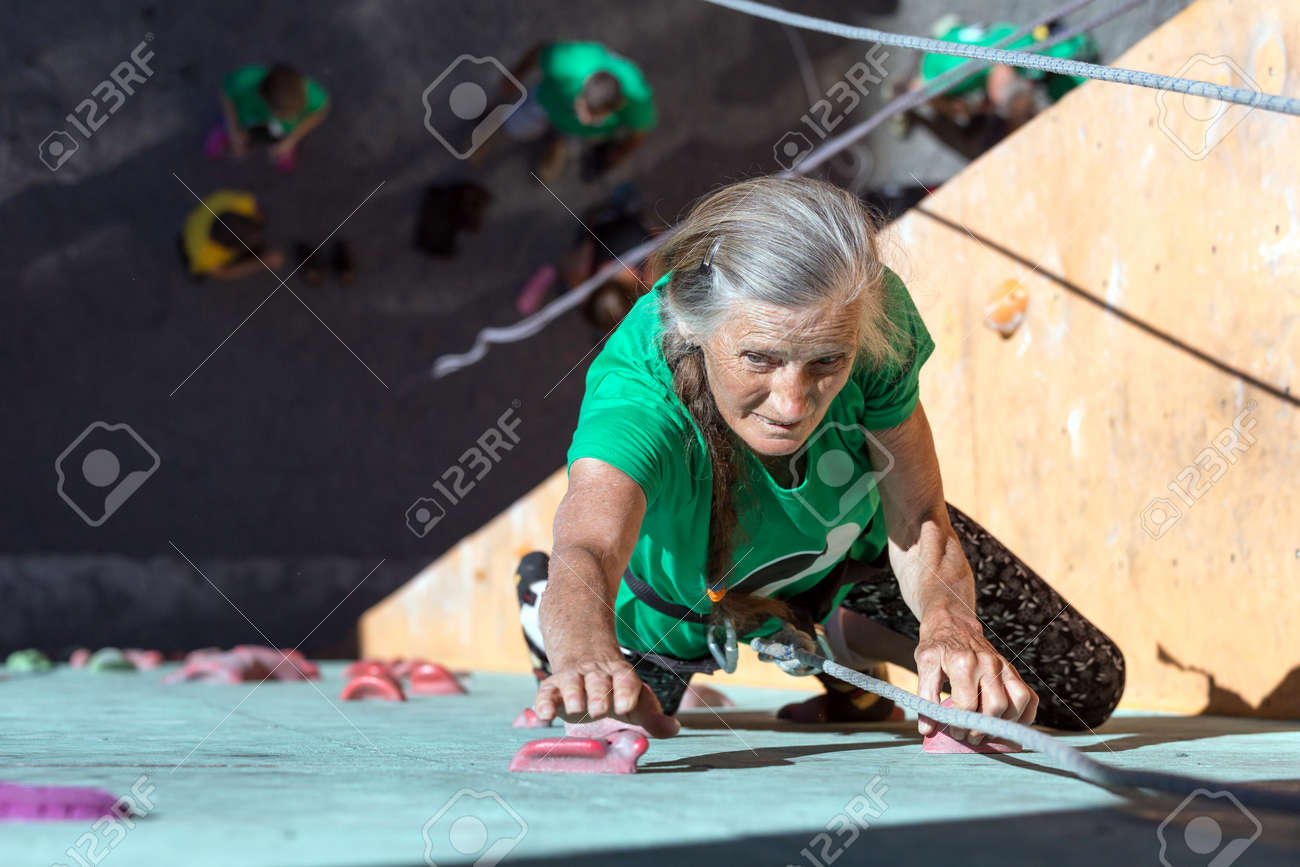 Elderly Female Demonstrates Excellent Physical and Mental Abilities Ascending Vertical Climbing Wall Group of Climbers Staying Below on Ground - 56954842