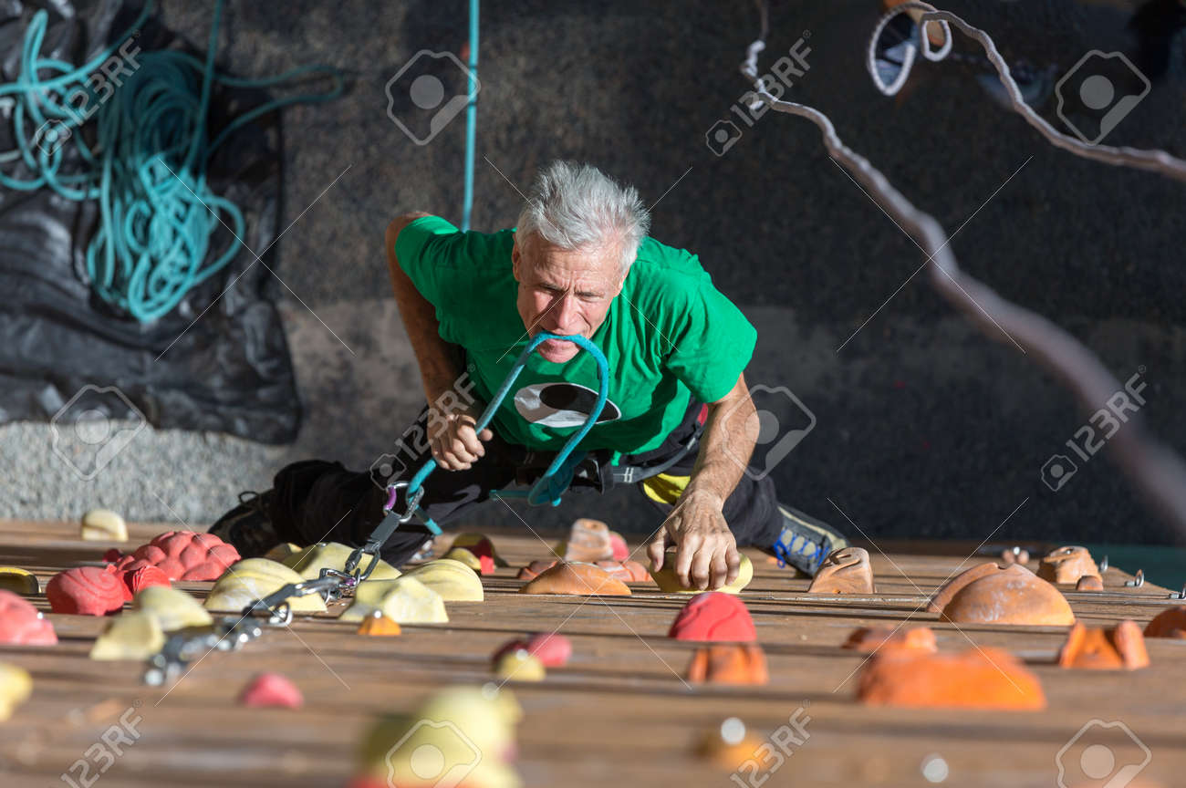 Aged Male Climber Moving Up on Outdoor Climbing Wall on Veterans Extreme Sport Competitions - 56954869