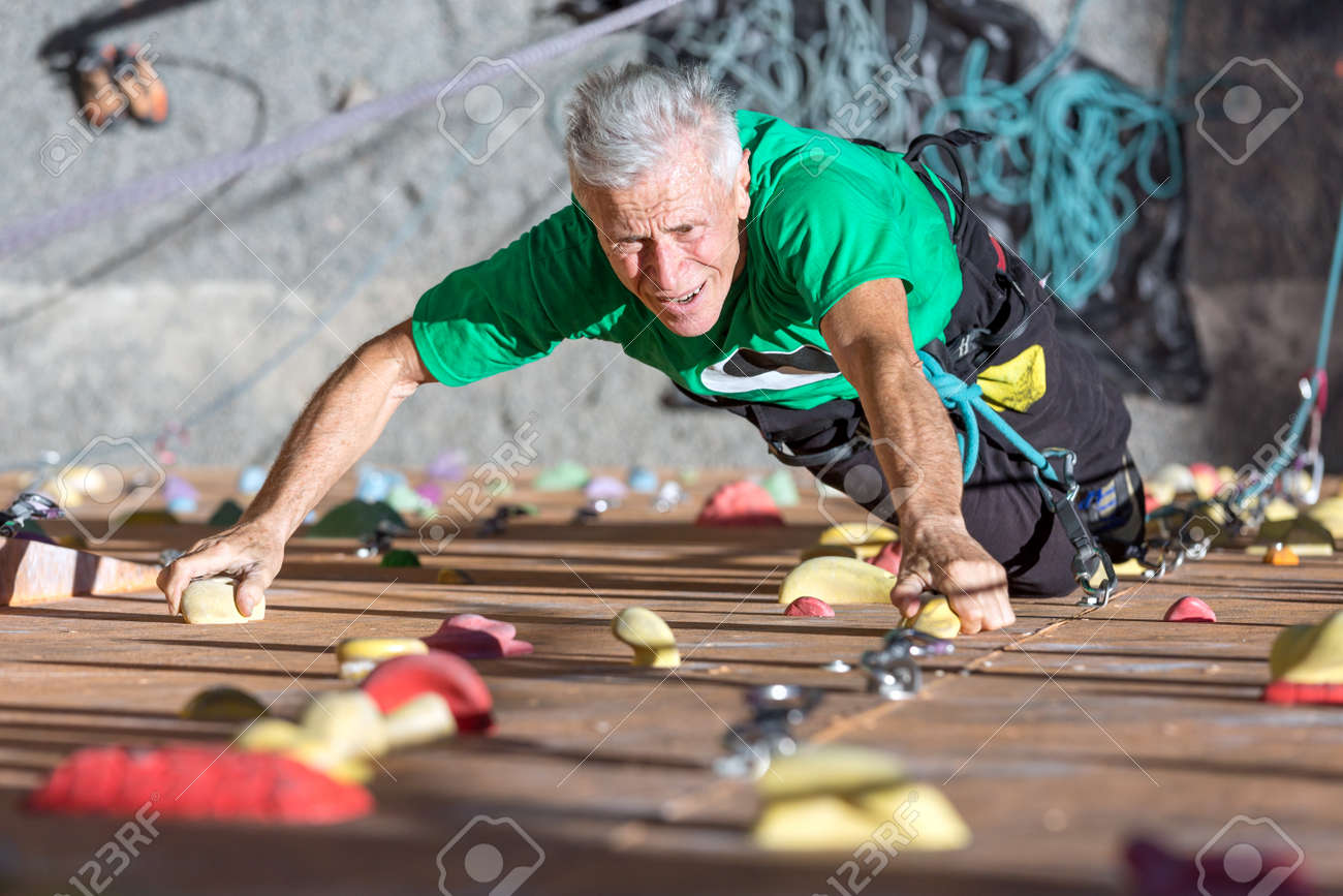 Portrait of Mature Male Climber Moving Up on Outdoor Climbing Wall Sporty Clothing on Fitness Training Intense but Positive Face Using Rope and Belaying Gear - 56954873