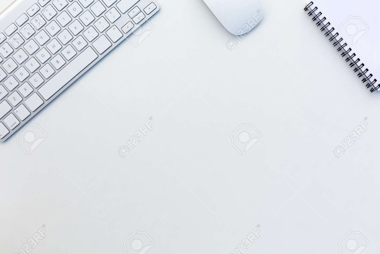 Image of White Office Desk with Computer Keyboard Mouse and Notepad from above - 58849564