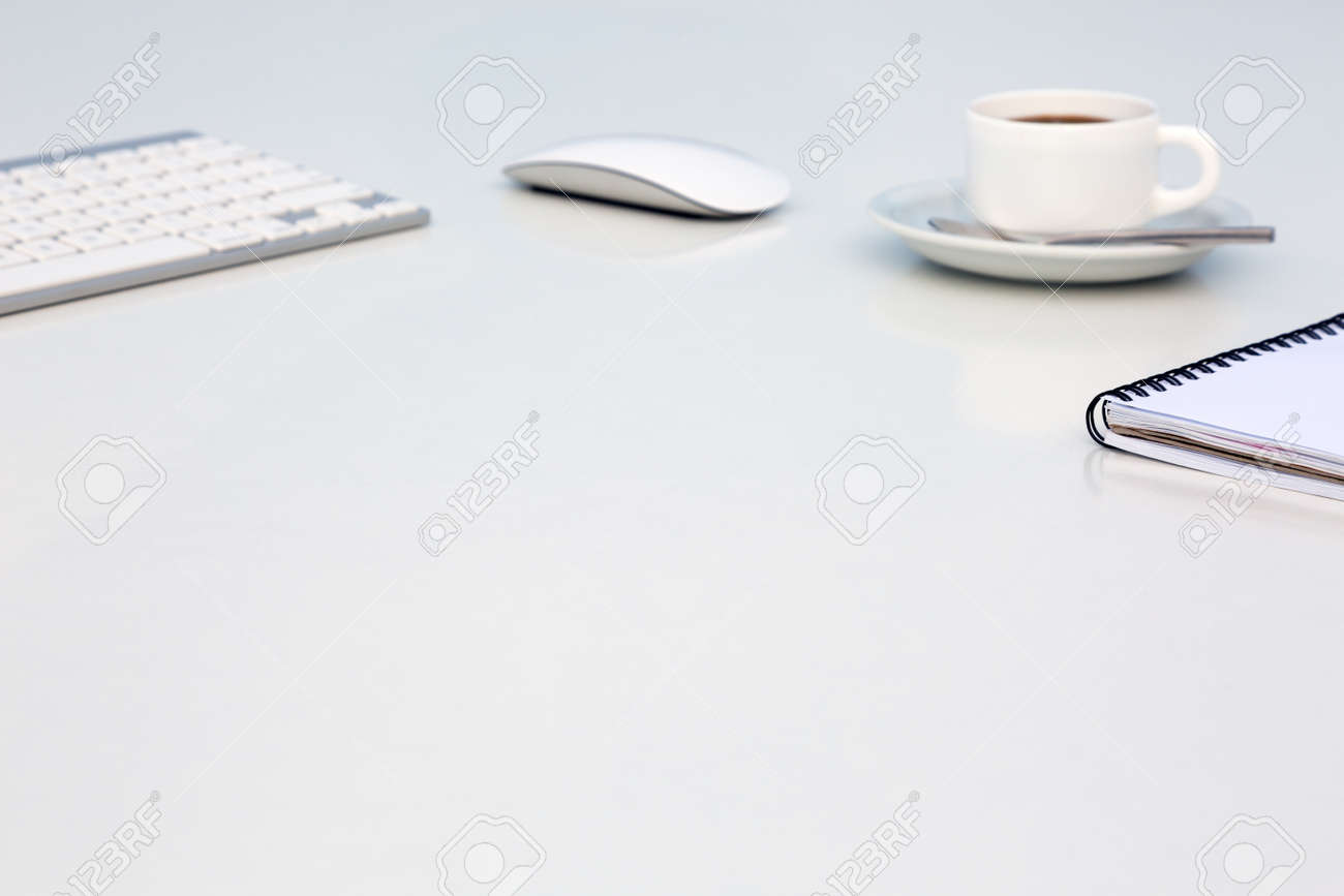 Bright open space office white table with coffee mug opened