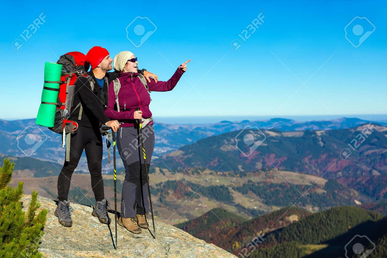 design de qualité 594cd 292e2 Randonneurs Homme et Femme avec sac à dos sportif Vêtements et Bâtons  Rester sur Top Rock et pointage Hands avec Mountain View