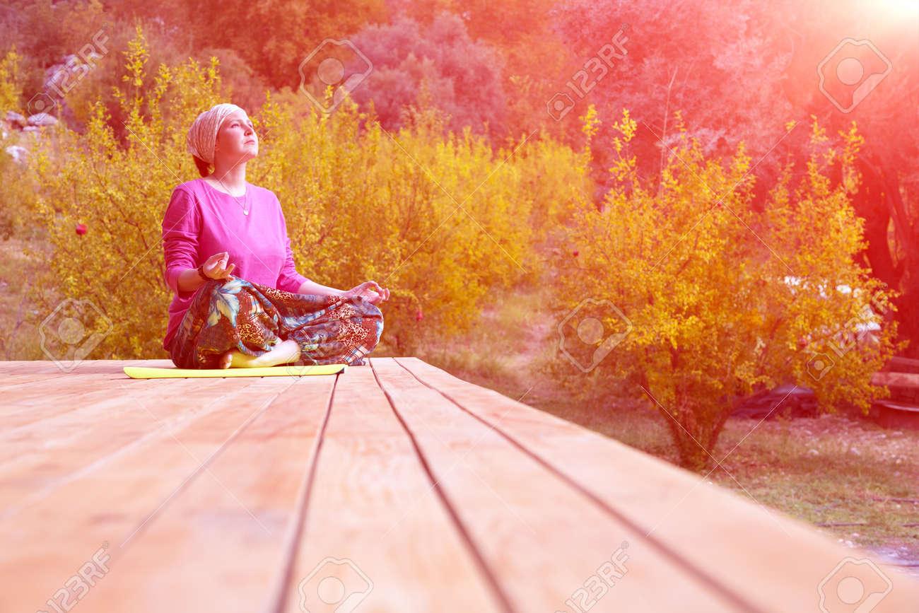 Persona Que Hace Ejercicio De Yoga En La Terraza De Madera De La Cabaña Rural Con El Jardín De La Granada En El Fondo Sol Que Brilla
