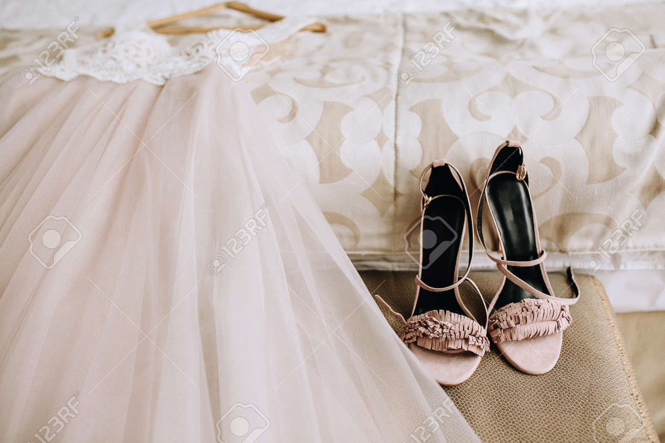 Pink Elegant Bride Shoes Next To A Beautiful Wedding Dress Lies
