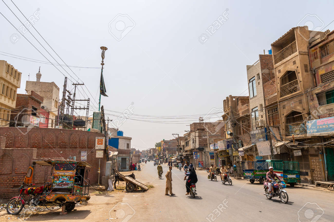 Multan Inner City Street Picturesque View with Rickshaw Walking People and Motorbikes on a Sunny Blue Sky Day - 136482922
