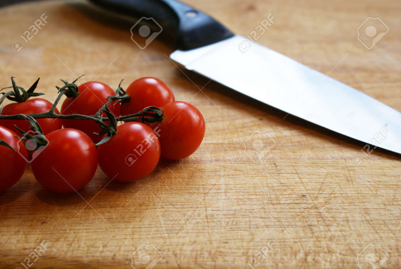 A knife and cherry tomatoes on the vine on a wooden chopping board Stock Photo - 13261036