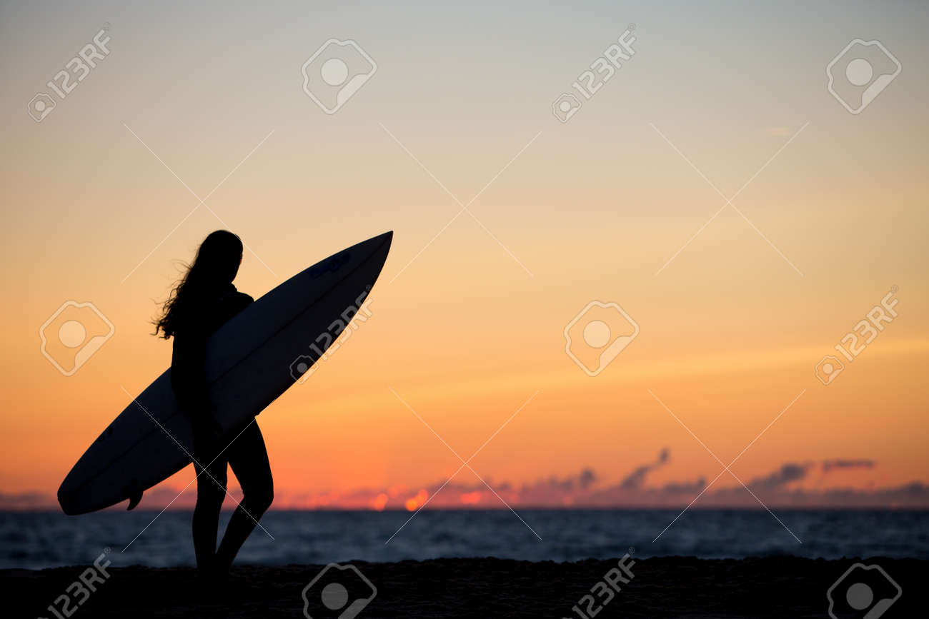700c819d3f silhouetted surfer girl in sunset at beach Stock Photo - 36912726