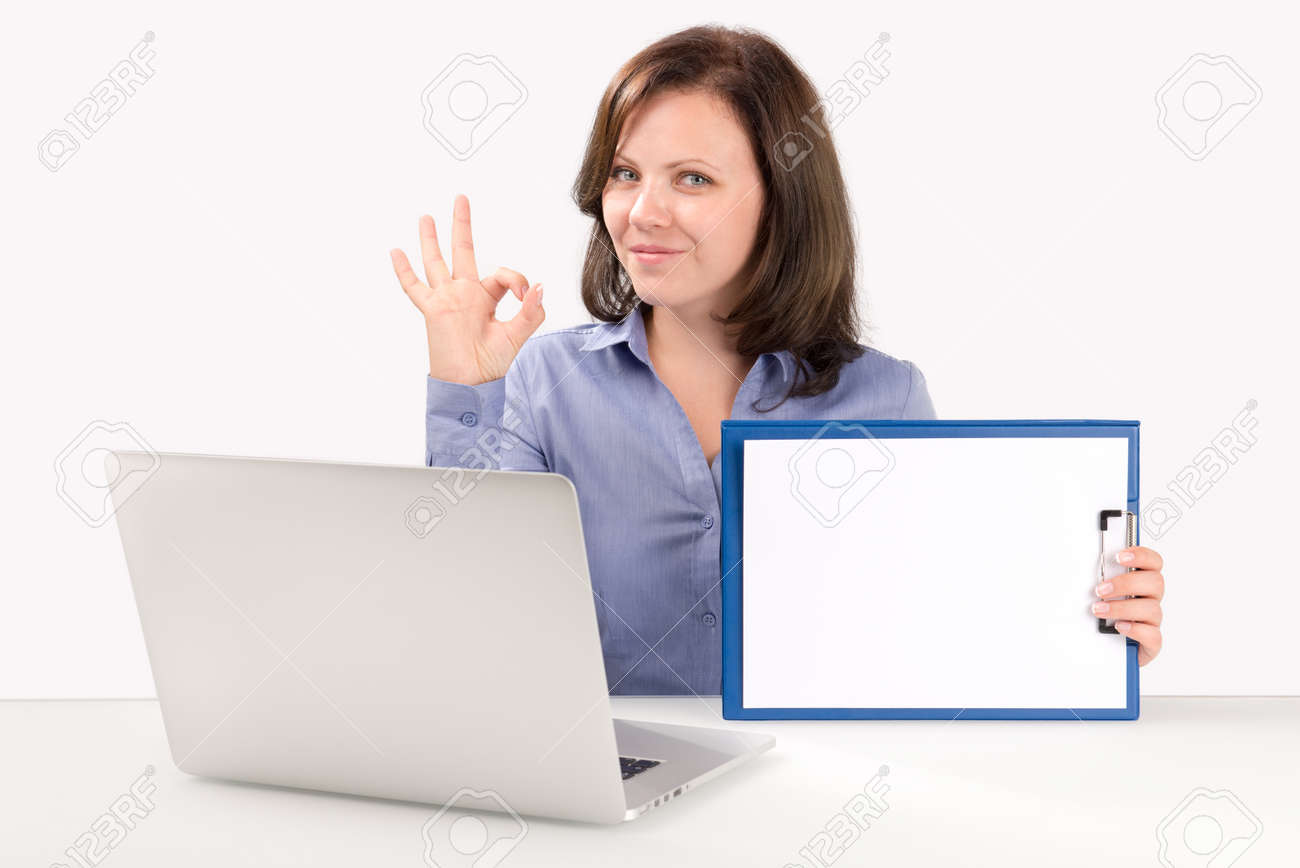 Business woman is sitting in front of a modern laptop with a blank clipboard and showing ok gesture, business concept Stock Photo - 22470618
