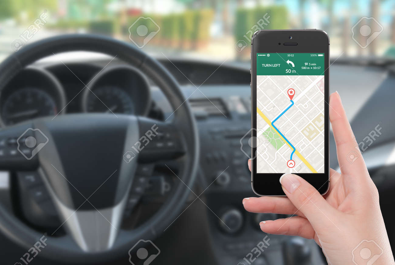 Female driver sitting in the car and holding black mobile smart phone with map gps navigation application with planned route on the screen. Blurred car interior on the background. - 32493059