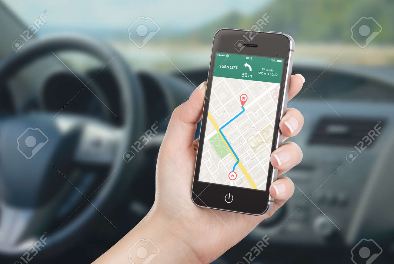 Female driver sitting in the car and holding black mobile smart phone with map gps navigation application with planned route on the screen. Blurred car interior on the background. - 32493060