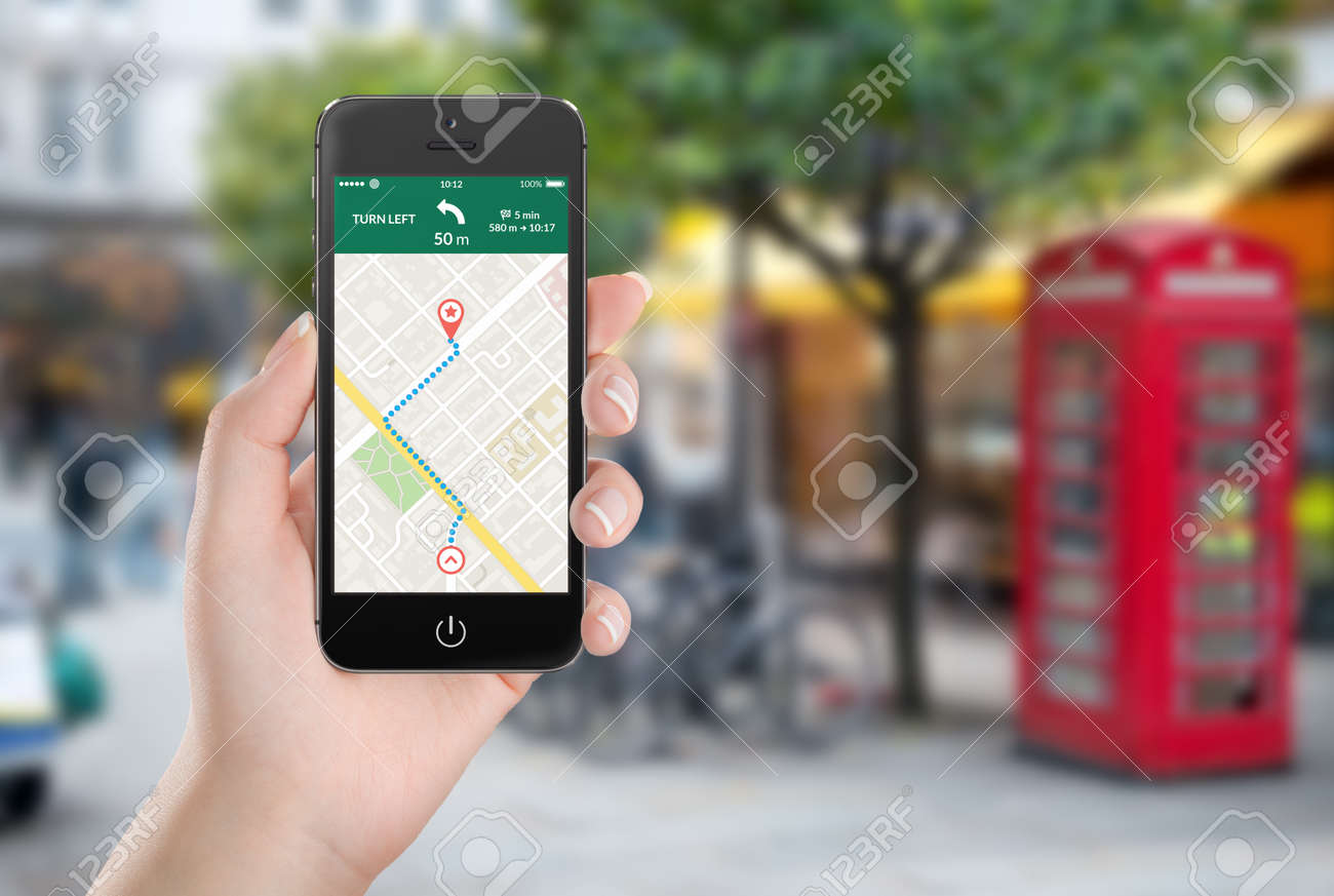 Female hand holding black mobile smart phone with map gps navigation application with planned route on the screen. Blurred street view on the background. - 32493094