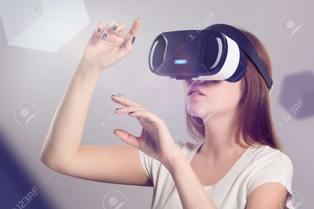 Woman in VR headset looking up and trying to touch objects in virtual reality. VR is a computer technology that simulates a physical presence and allows the user to interact with environment. - 55674443