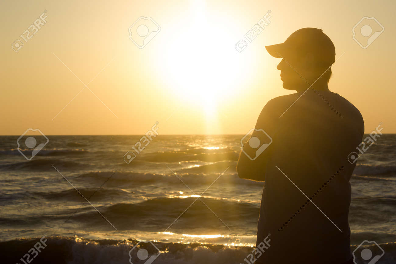 Portrait of a young man in cap on the beach - at sunrise - 149039177