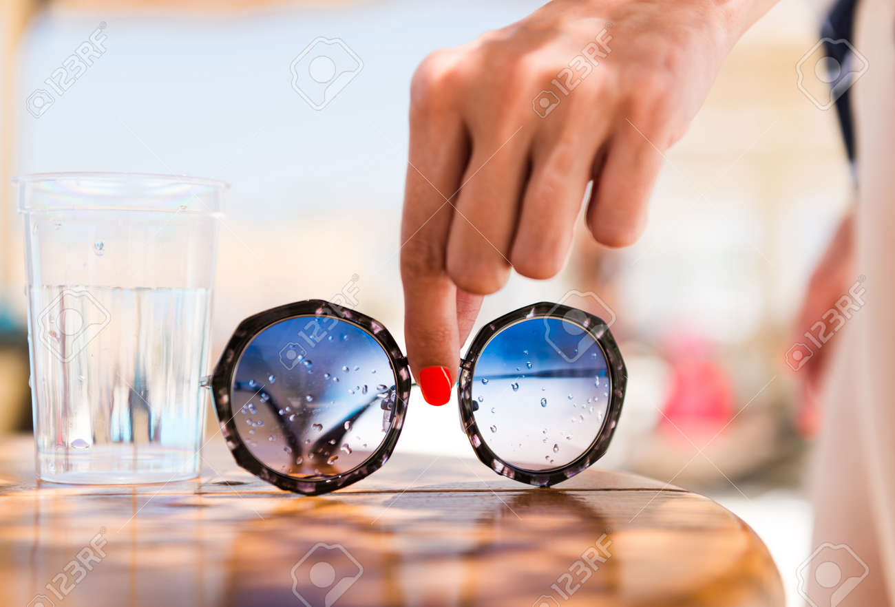 woman taking sunglasses from summer pool table - 127951892