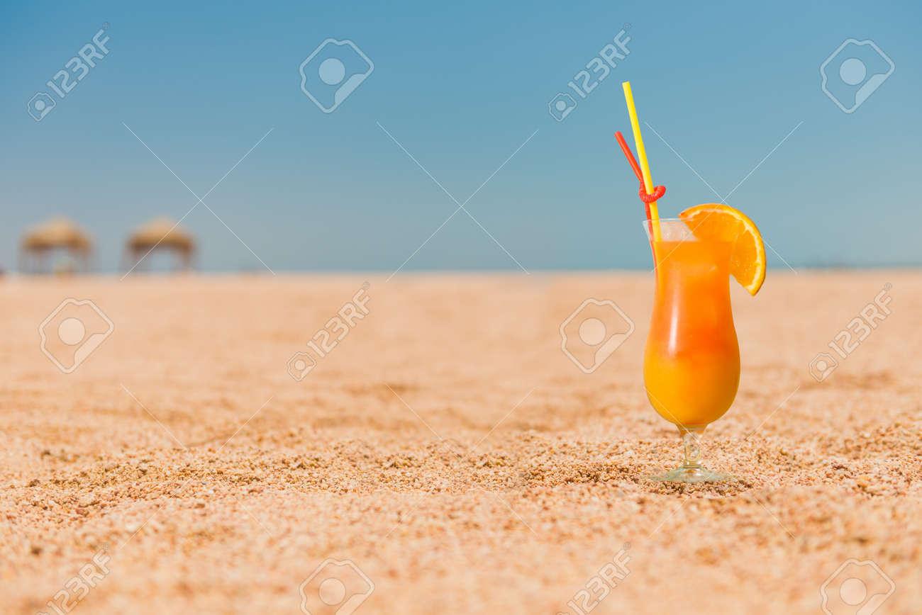 ocktail with orange juice on sandy beach - 137792544
