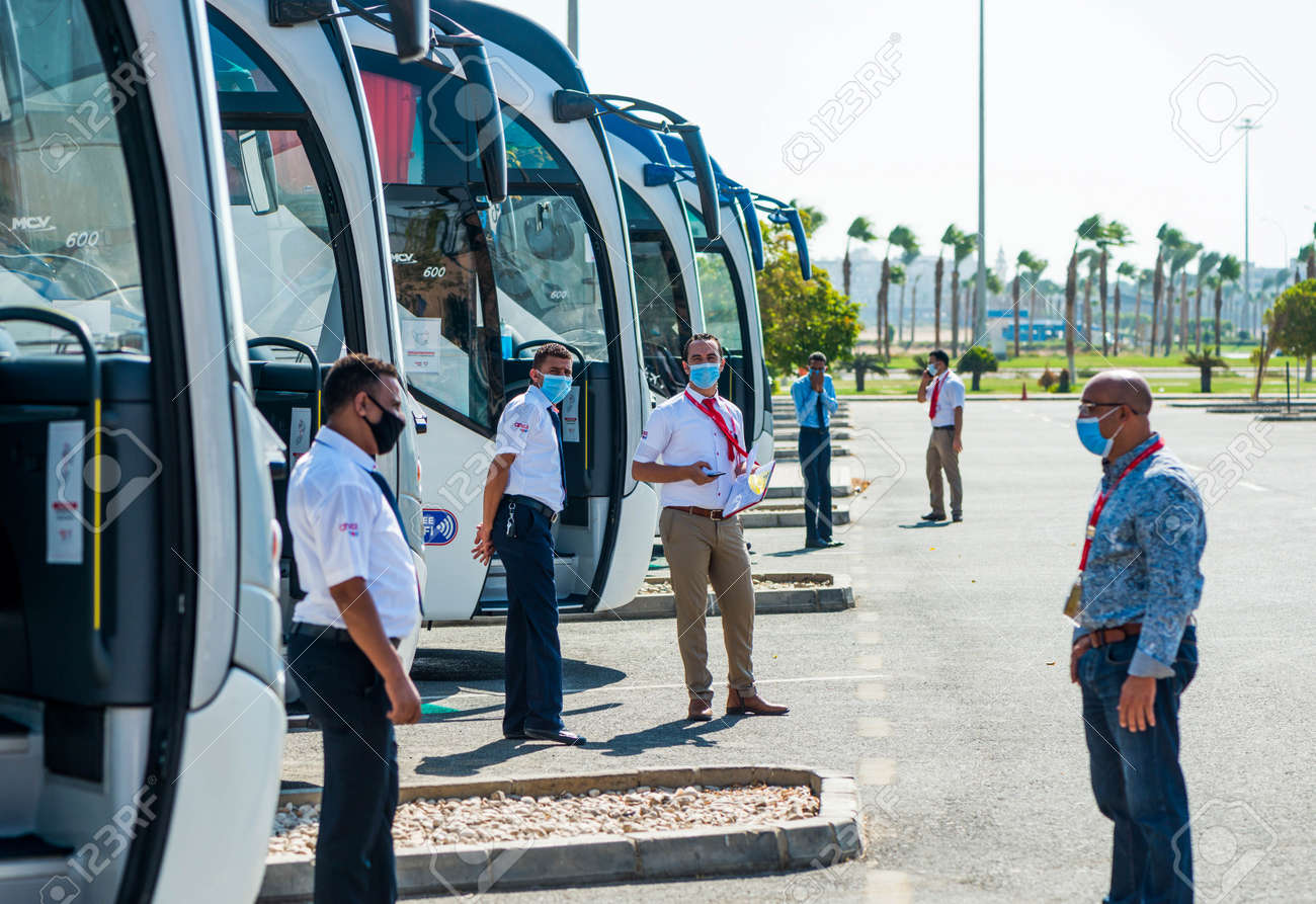Egypt, Hurghada - 07/11/2020. tour guides in protective masks waiting for tourists at buss station near airport - 154118507
