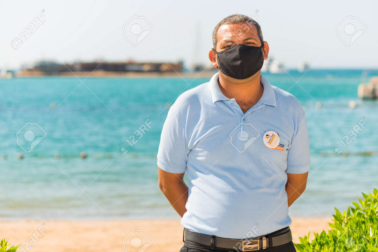 Egypt, Hurghada - 07/15/2020. friendly portrait of egyptian hotel staff in pritective face mask at summer sea beach background - 154118503