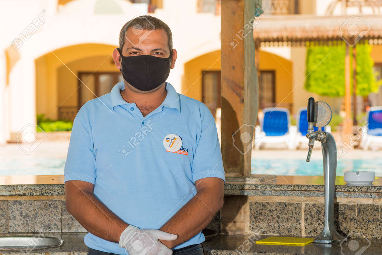 Egypt, Hurghada - 07/15/2020. friendly portrait of egyptian hotel staff in pritective face mask at summer sea beach background - 154118502