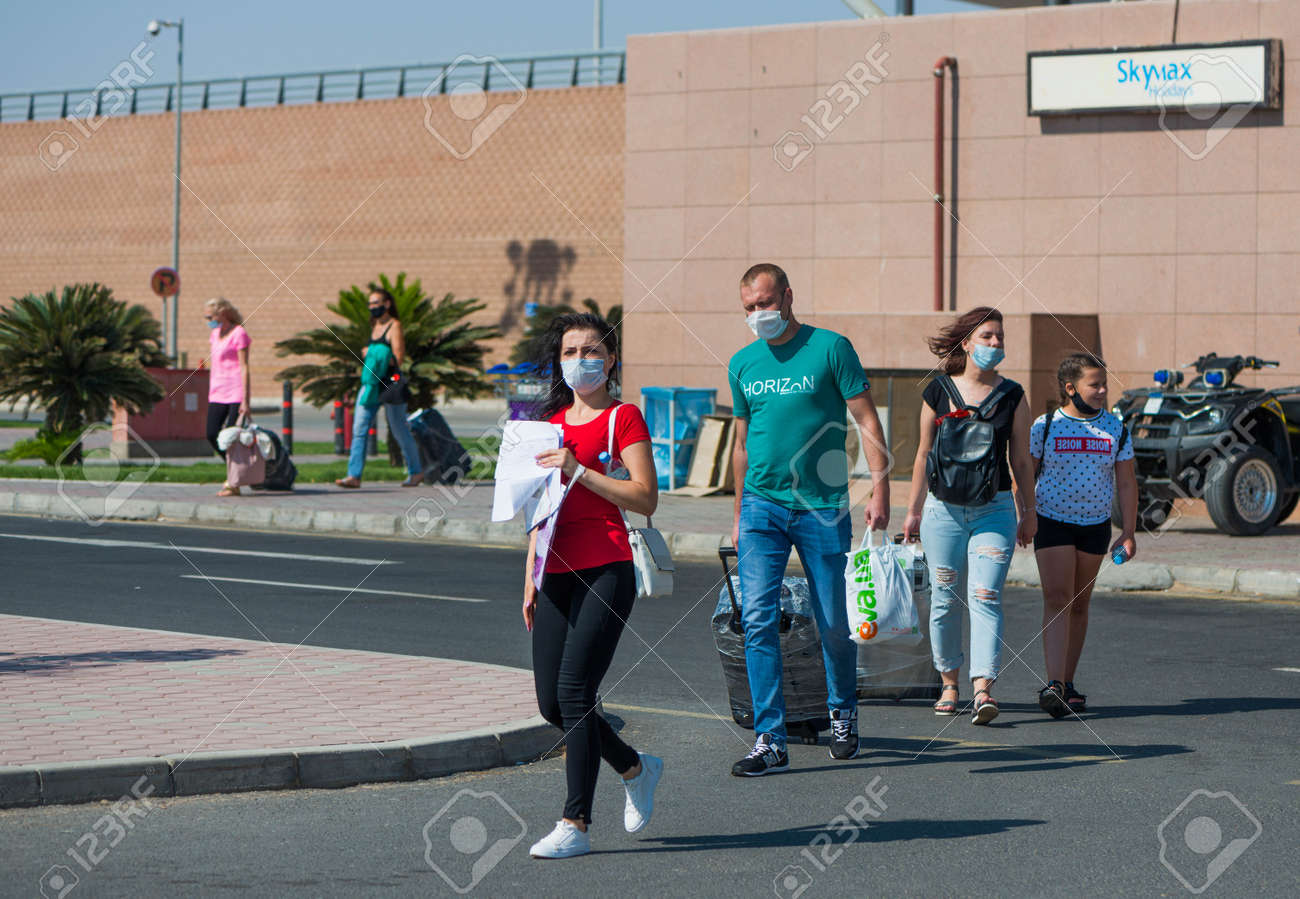 Egypt, Hurghada - 07/11/2020. tourists in protective masks after arriving leaving airport area - 154118505