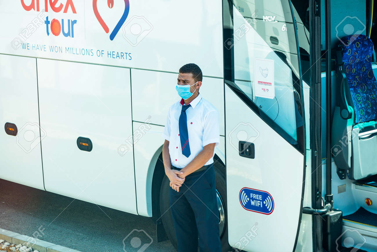 Egypt, Hurghada - 07/11/2020. tour guide in protective mask standing near buss entrance waiting for tourists - 154118504