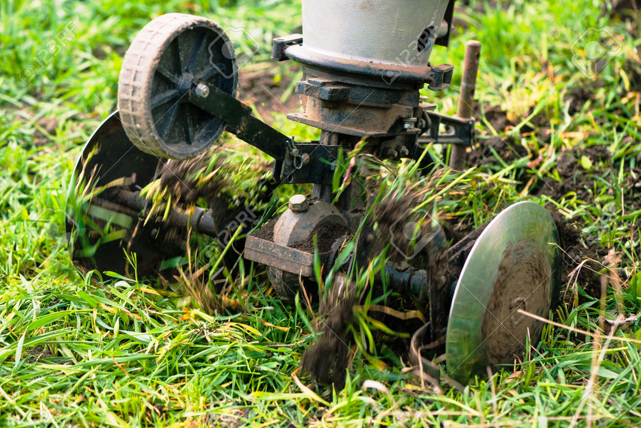 plowing machine working with soil at springtime farmland - 169120989