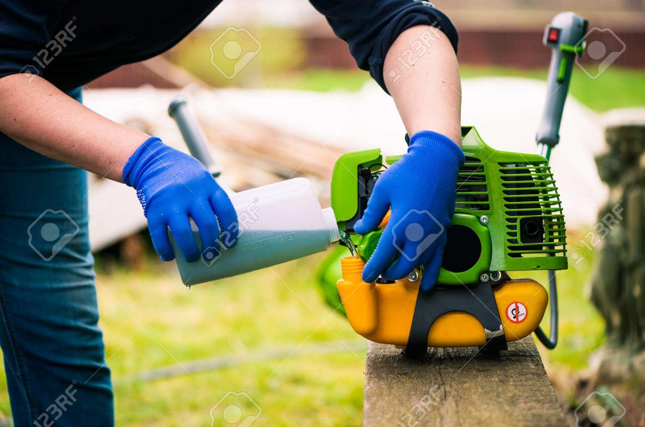 grass-cutter preparing to work on spring farmland soil - 169120990
