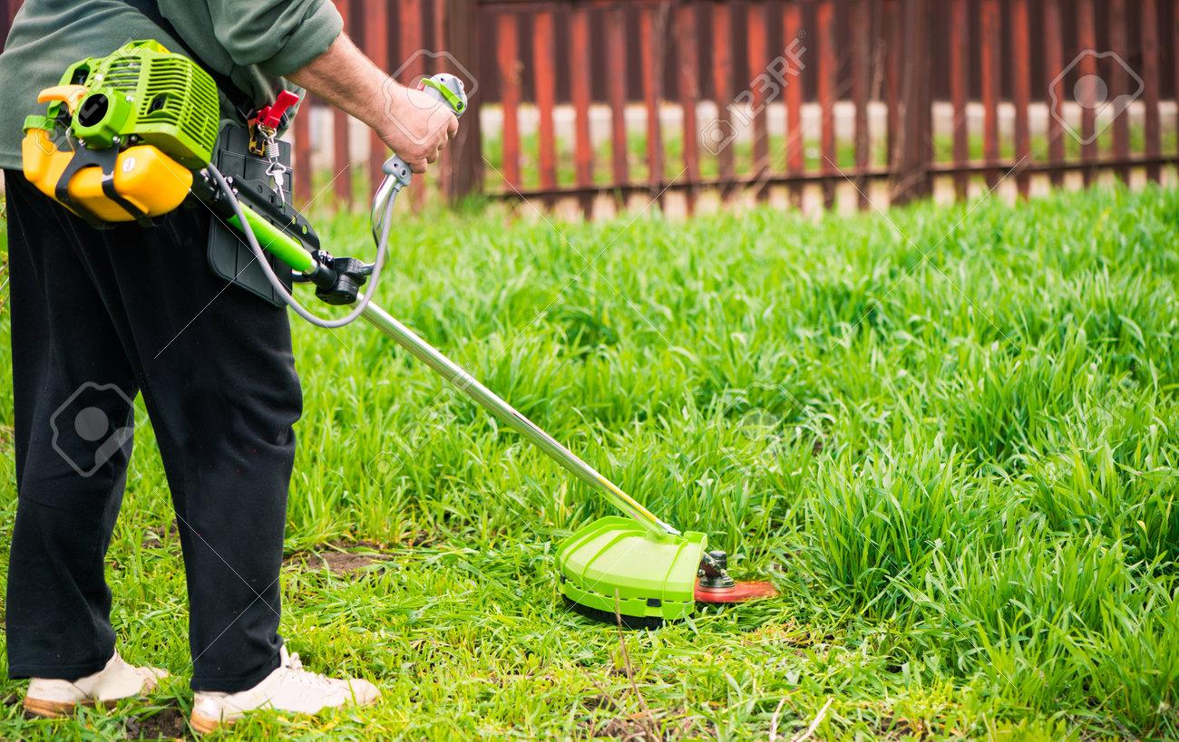 farmer working with grass-cutter on spring farmland soil - 169122095