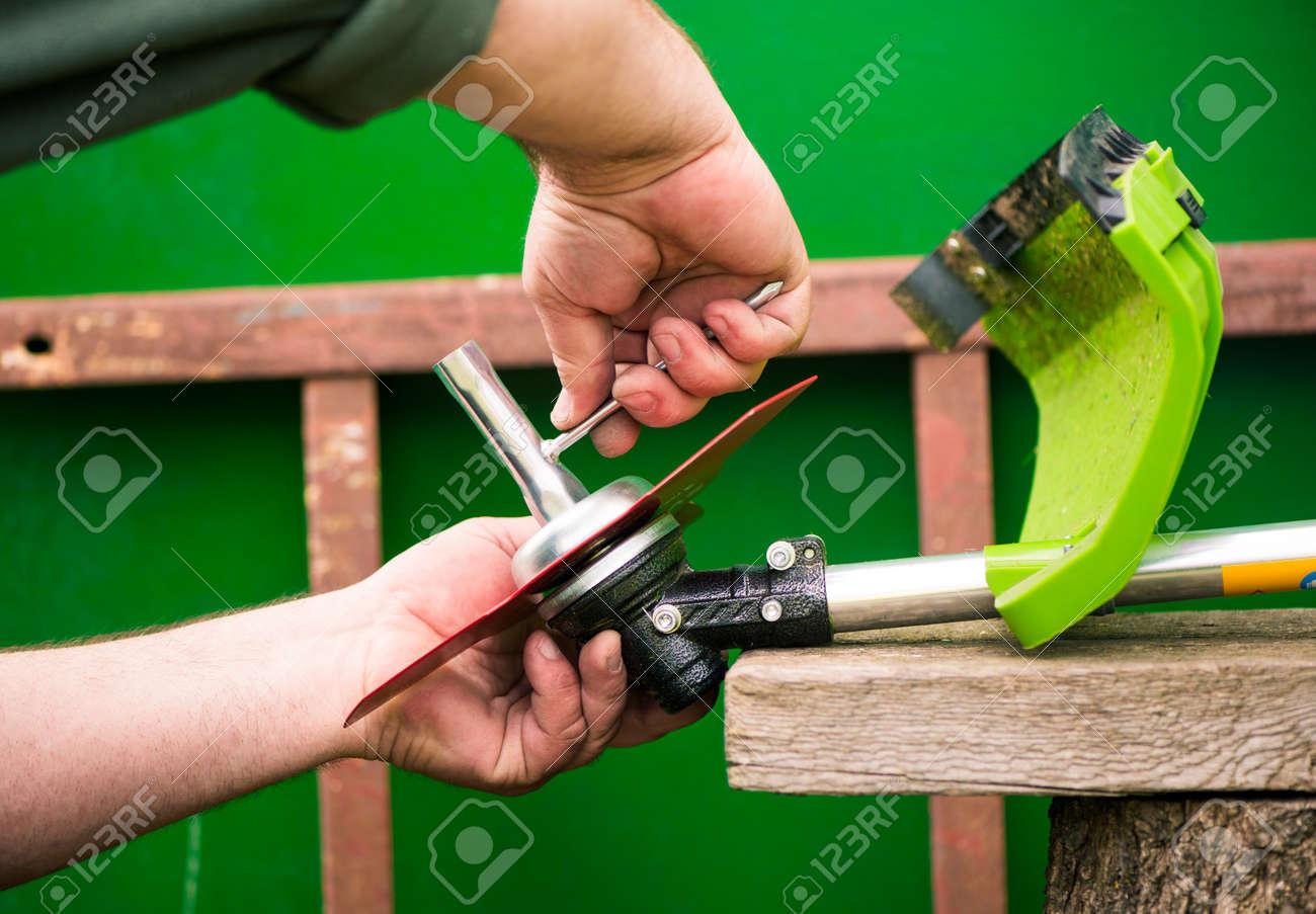 grass-cutter preparing to work on spring farmland soil - 169122099