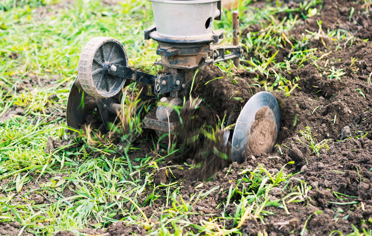 plowing machine working with soil at springtime farmland - 169122100