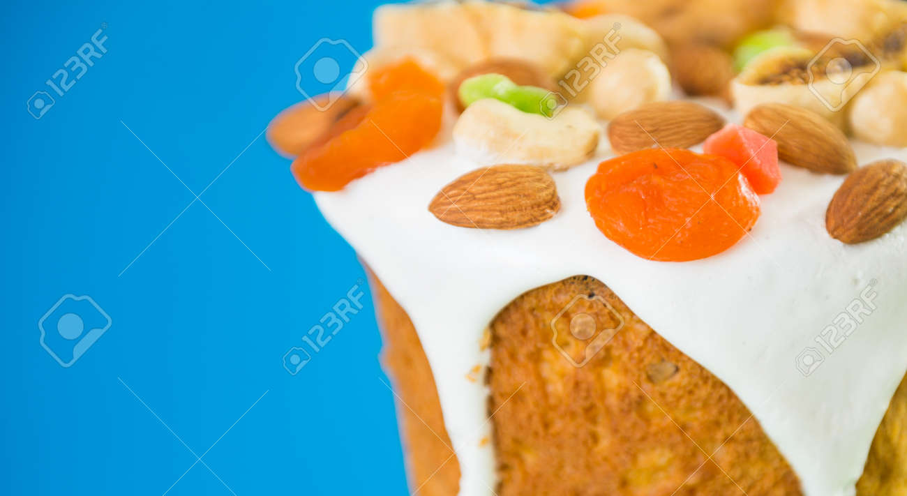 Easter holiday cake decorated with fruits and nuts isolated on blue background - 169122114