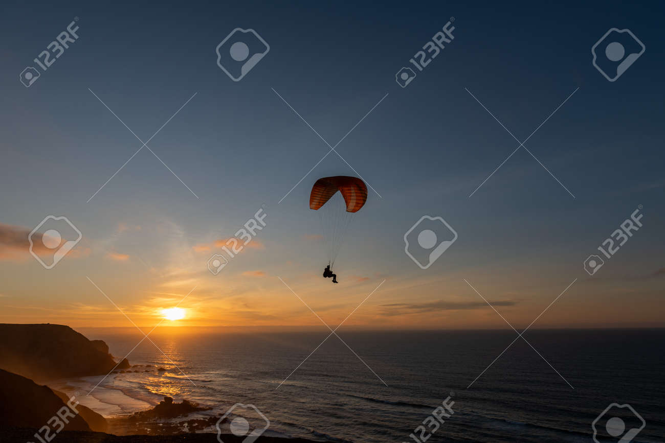 Paraglider flying over thesea shore at sunset. Paragliding sport concept. - 144765517