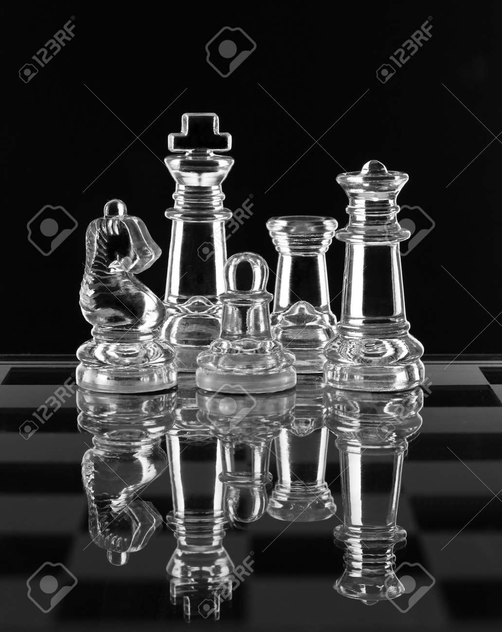 Glass chess family with reflection on black background Stock Photo - 12834345