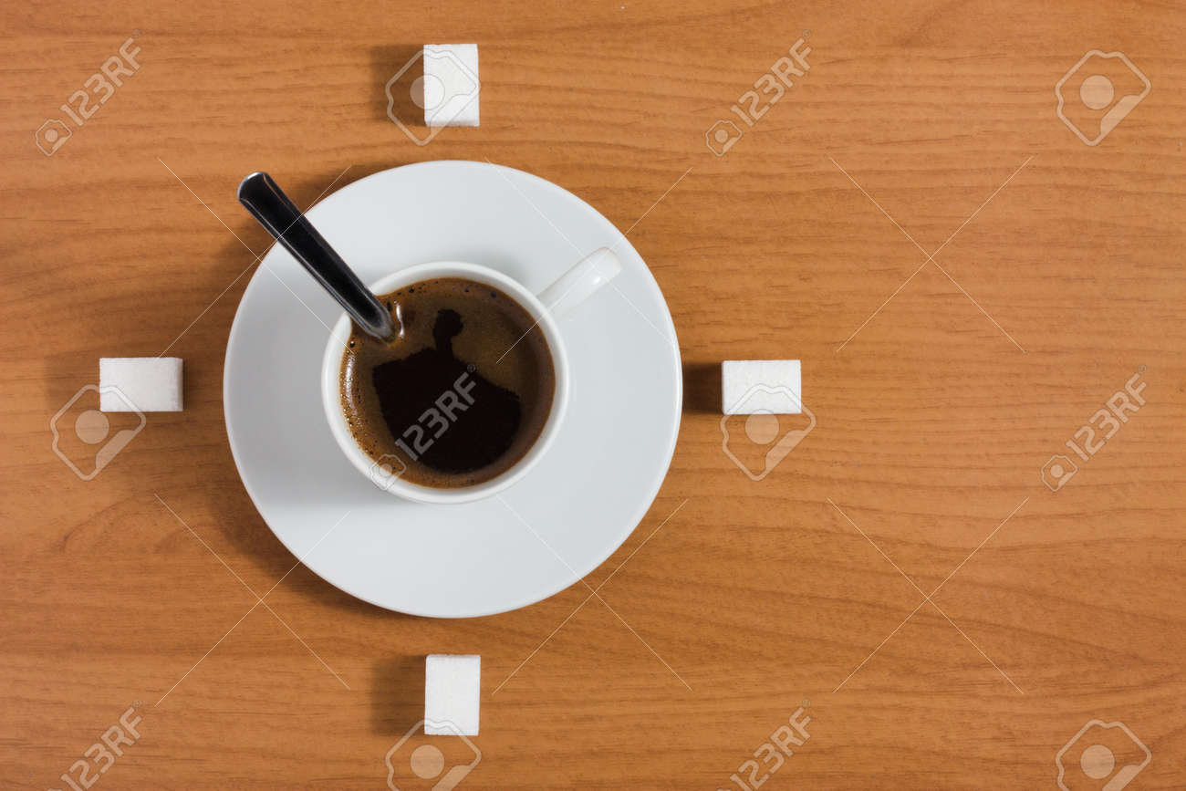 White coffee cup with saucer and sugar like a clock on a wooden brown table, top view - 15794613