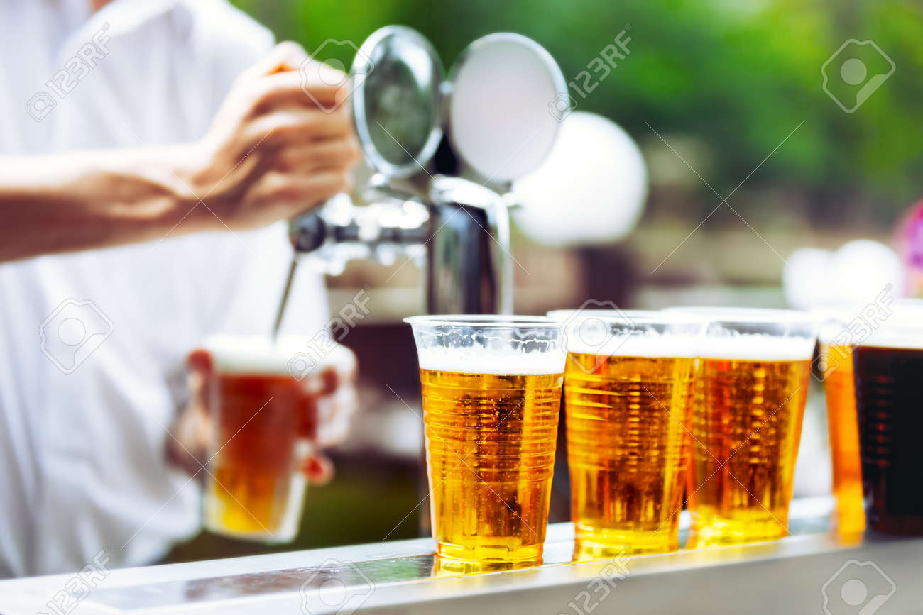 Man drawing beer from tap in an plastic cup. Draught beer. The bartender pours a beer in a plastic cup. On the bar table are plastic cups with a beer - 51065242