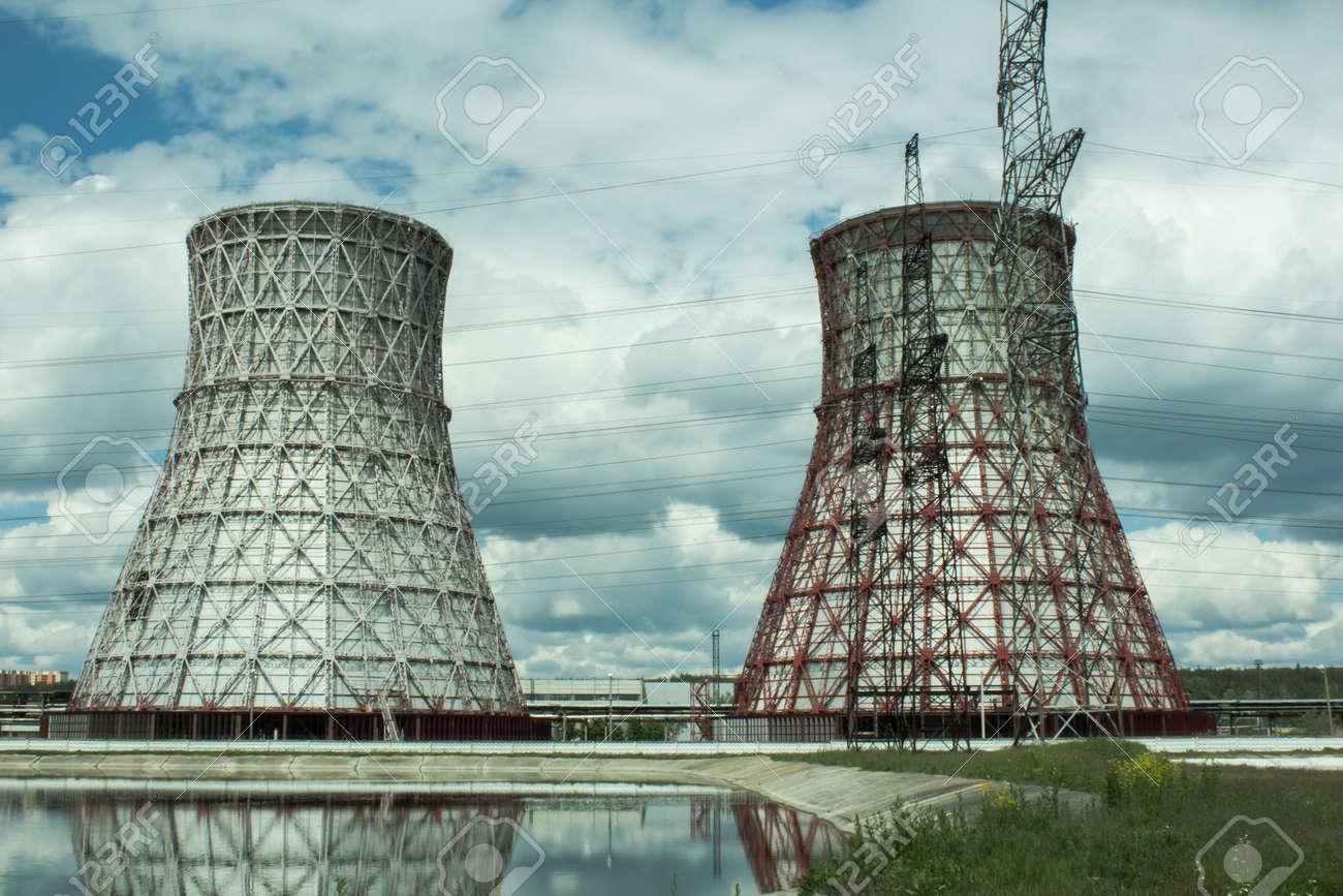 View of the power plant and cooling towers. The smoke goes out from a cooling tower of an operating power station. Cooling towers of a thermoelectric power station are reflected in a technical reservoir. Concept of ecology, environmental protection. - 148540441