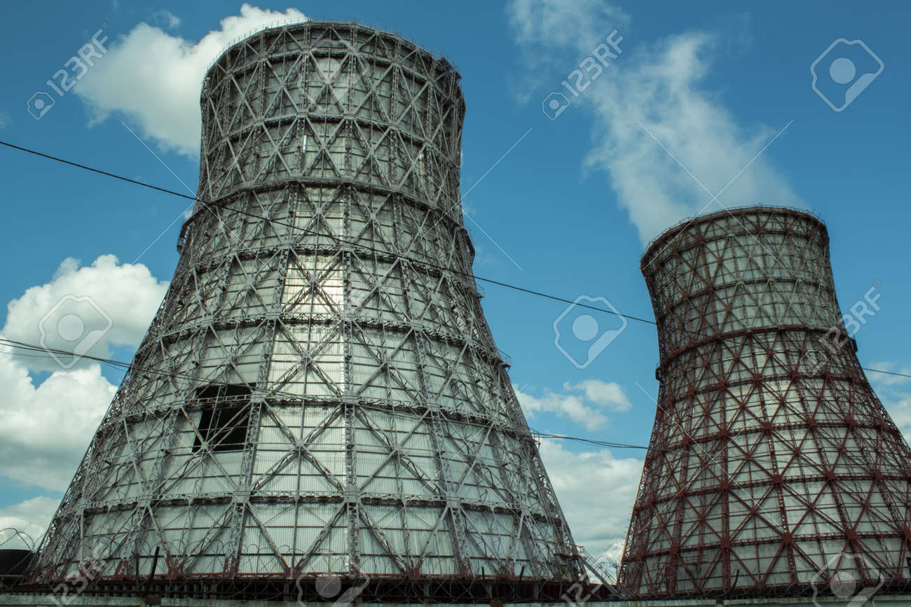 View of the power plant and cooling towers. The smoke goes out from a cooling tower of an operating power station. Cooling towers of a thermoelectric power station are reflected in a technical reservoir. Concept of ecology, environmental protection. - 148538669