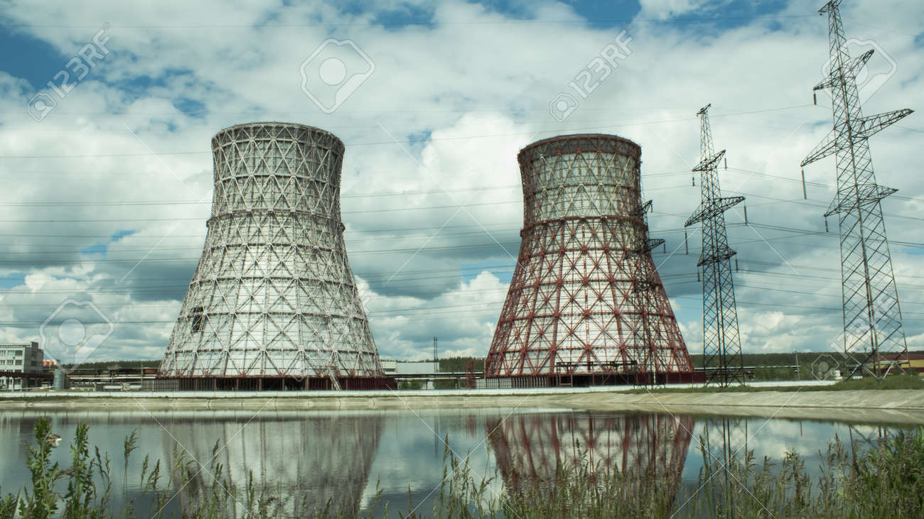 View of the power plant and cooling towers. The smoke goes out from a cooling tower of an operating power station. Cooling towers of a thermoelectric power station are reflected in a technical reservoir. Concept of ecology, environmental protection. - 148546725