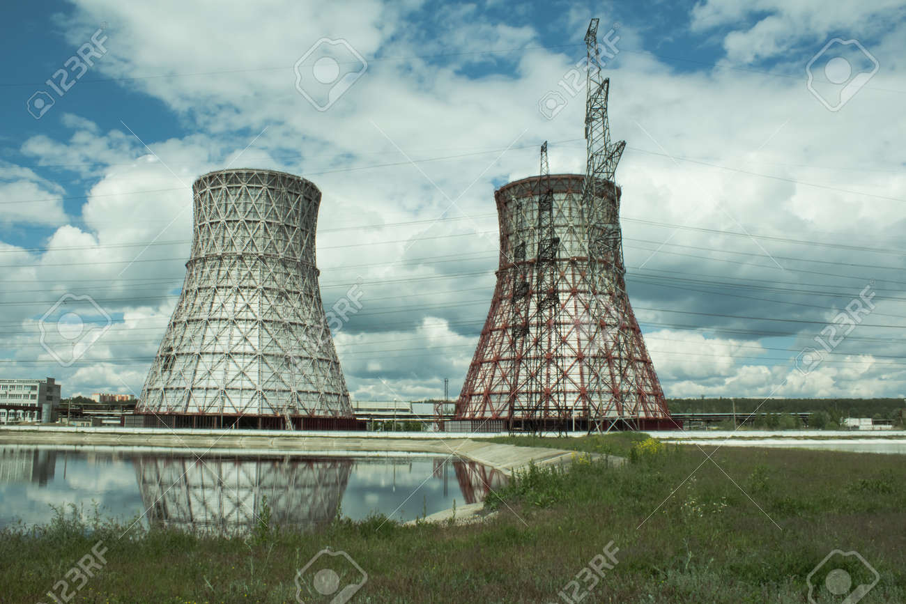 View of the power plant and cooling towers. The smoke goes out from a cooling tower of an operating power station. Cooling towers of a thermoelectric power station are reflected in a technical reservoir. Concept of ecology, environmental protection. - 148550826