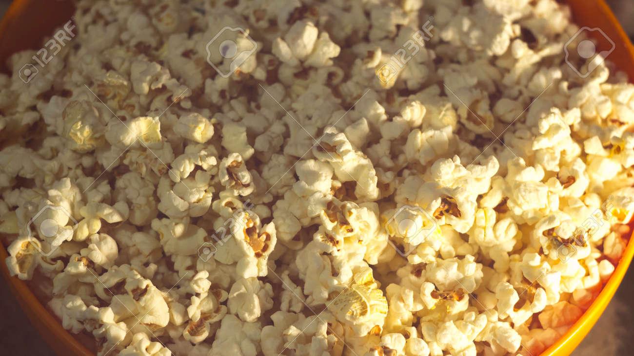 Fresh crispy popcorn lies in a bucket. Fresh hot popcorn lies in an orange bowl. Cinema pop corn background. - 148567127