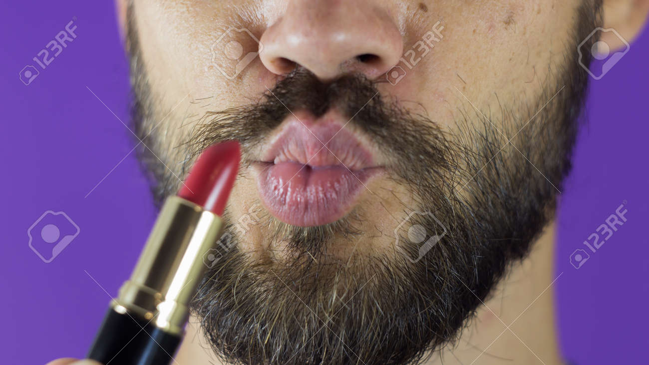 A young guy with a beard paints his lips with red lipstick. Close-up of a bearded man, he painted lips with bright lipstick. A bearded man puts red lipstick on his lips, smiles and smacks his lips. - 152947780