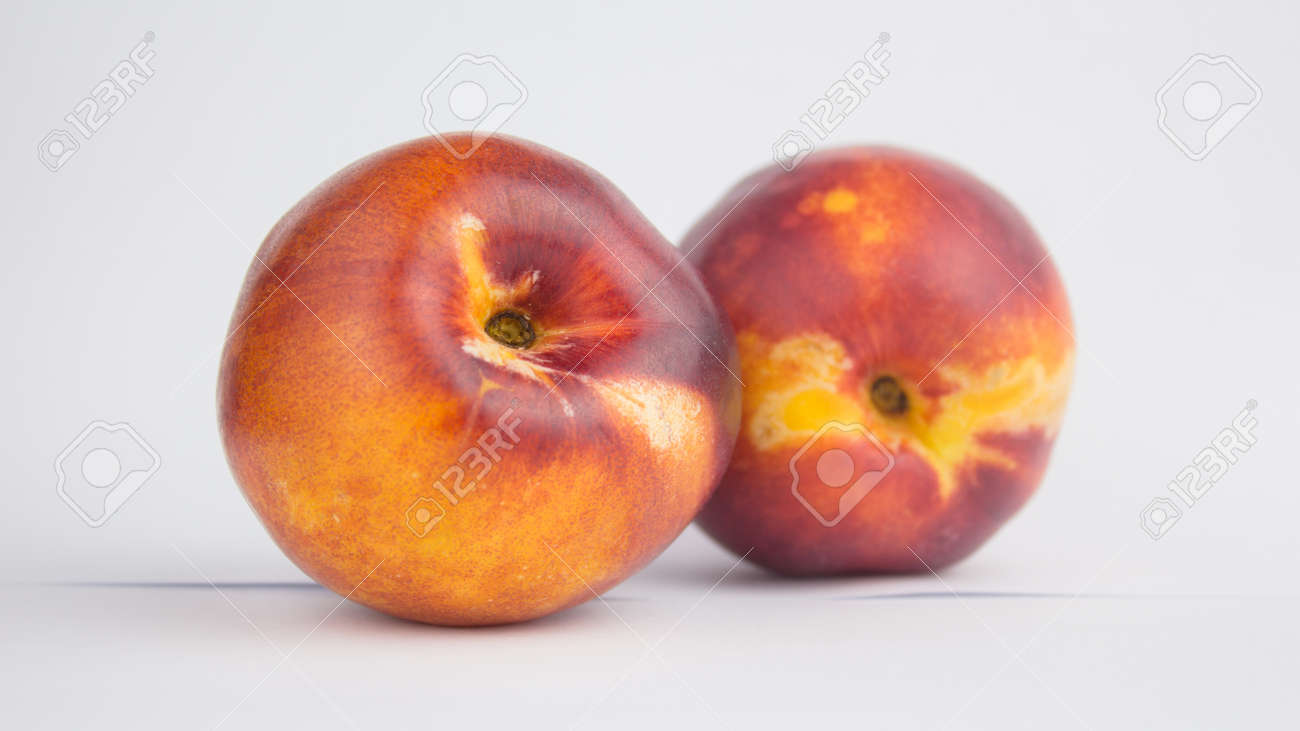 Fresh juicy peaches on a white plate. Close-up Fresh organic peaches nectarine on a white plate. - 152947789