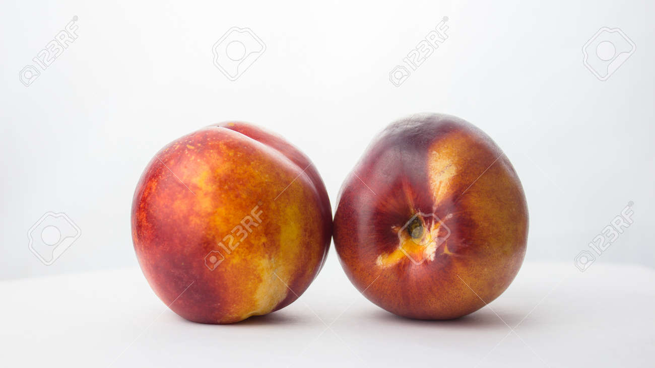 Fresh juicy peaches on a white plate. Close-up Fresh organic peaches nectarine on a white plate. - 152883655