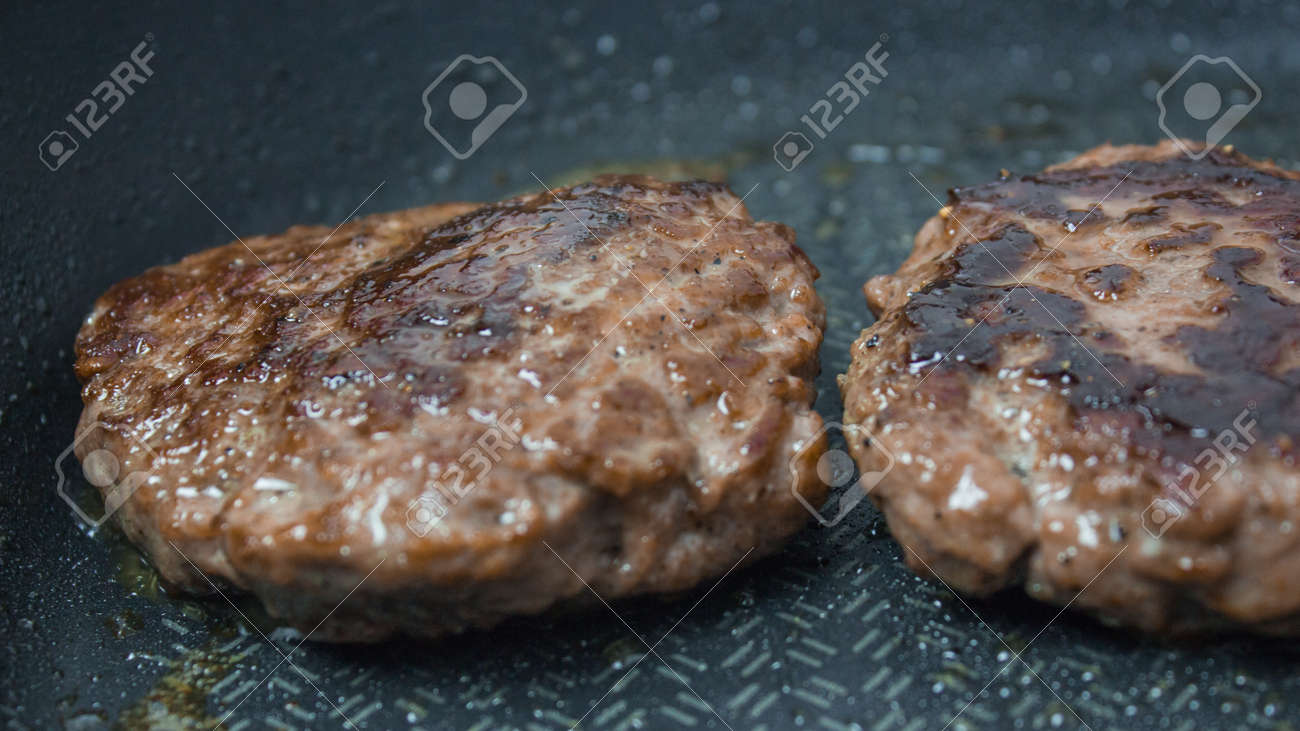A chef puts beef patties on the grill. A juicy beef cutlet, fried in a pan. Close-up of beef cutlet for a burger on the grill. - 152883722