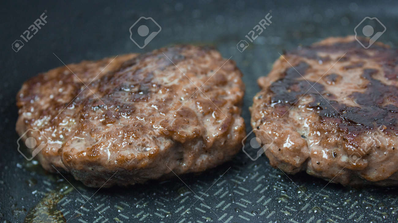 The chef puts beef patties into a frying pan. Juicy beef cutlet is fried in a pan. - 152885130