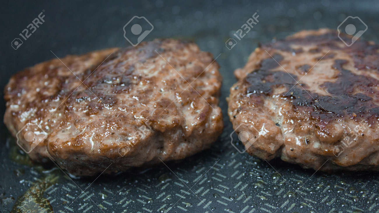 A chef puts beef patties on the grill. A juicy beef cutlet, fried in a pan. Close-up of beef cutlet for a burger on the grill. - 152885370