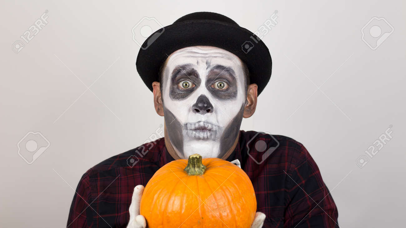 A horrible man in clown make-up holds a pumpkin, symbol of Halloween. A scary clown looks at the camera, holds a pumpkin in his hands and threatens her with a knife. Halloween costume. - 157074207