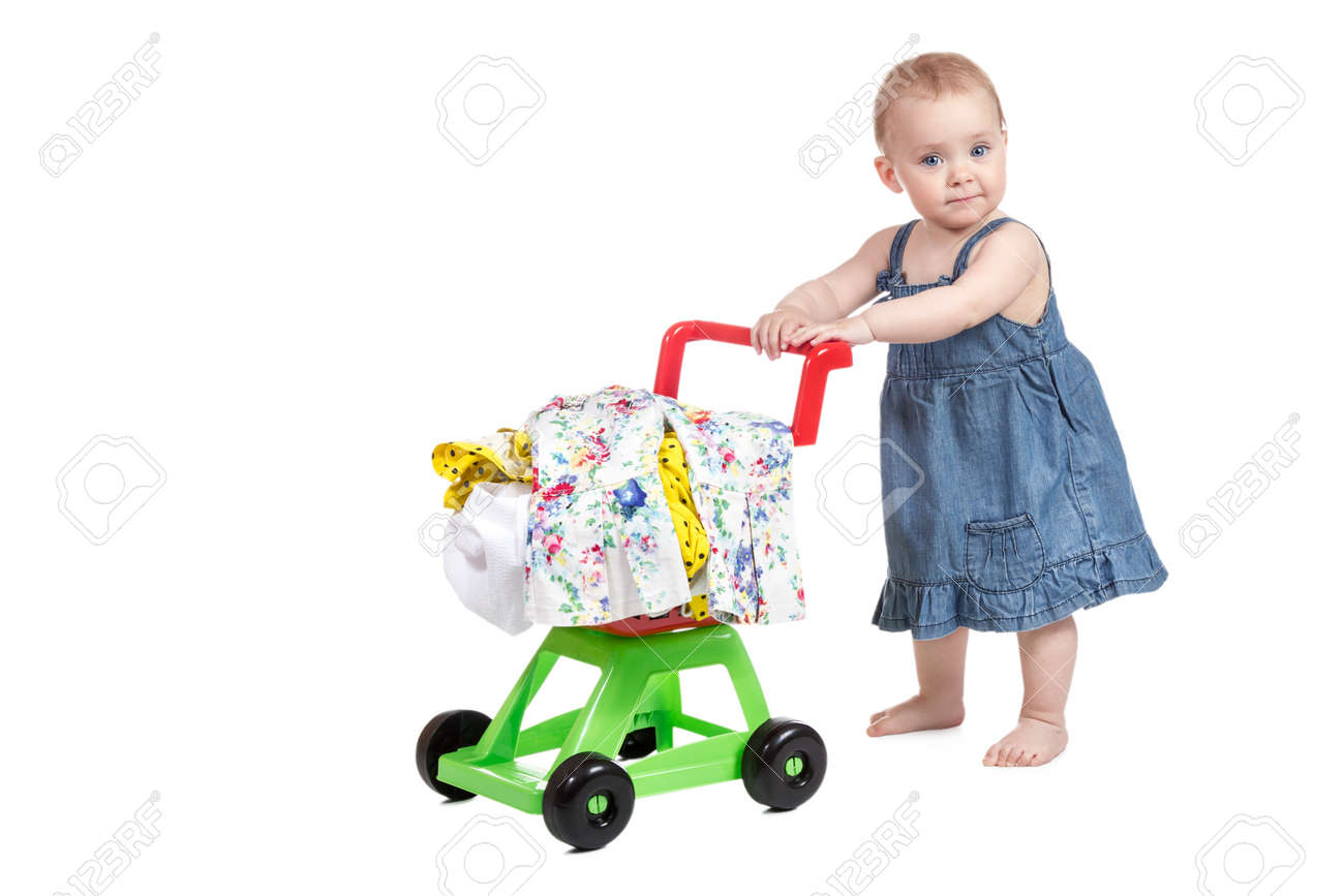 Little girl in denim dress driven child plastic shopping trolley full of clothes isolated on white background - 39951278